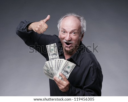 Happy old man with money showing yes sign on a grey background - stock photo
