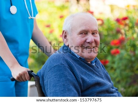 Happy old patient sitting in wheelcharis, in the garden. - stock photo
