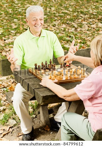 Happy old people playing chess in the park.