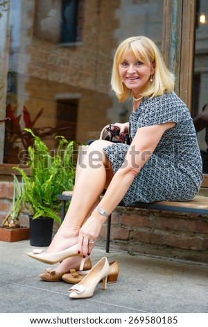 Happy old senior blonde woman 60-65 years, sitting on bench in downtown city put high heel shoes on her feet - stock photo