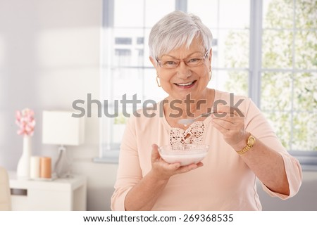 Happy old woman eating breakfast cereal, smiling, looking at camera. - stock photo