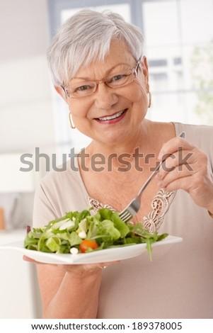 Happy old woman eating fresh green salad, smiling, looking at camera. - stock photo