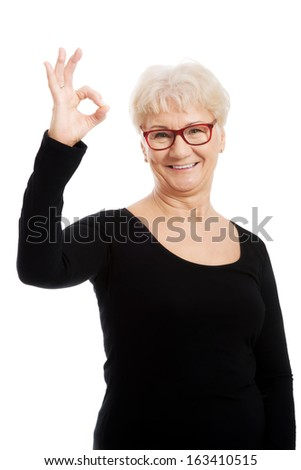 Happy old woman in eye glasses showing OK. isolated on white.