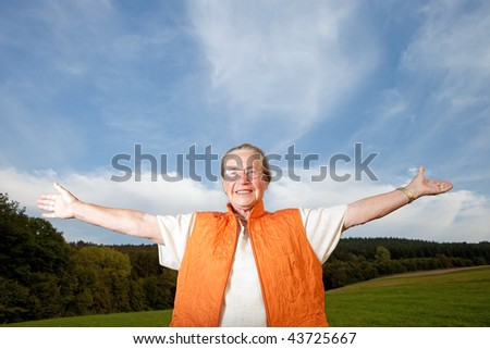 Happy old woman on a meadow