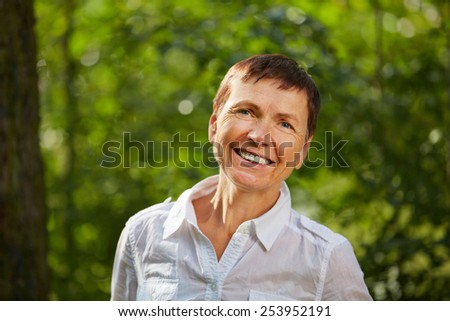 Happy old woman standing in summer in nature in a forest