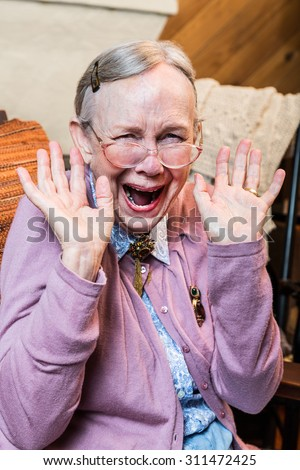 Happy old woman with a hands up gesture - stock photo