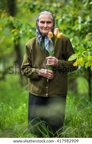 Happy old woman with flowers outdoor in the garden - stock photo