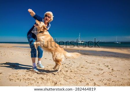 Happy older woman playing on the beach with golden retriever - stock photo