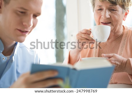 Happy older woman spending nice afternoon with her male caregiver - stock photo
