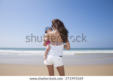 happy one year blonde baby in brunette woman mother arms back at beach Conil Cadiz Spain - stock photo