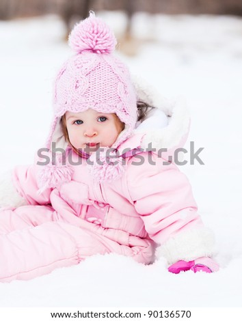 happy one year old baby girl  outdoor in the park  on a winter day - stock photo