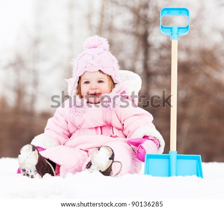 happy one year old baby girl with a toy spade outdoor on a winter day - stock photo