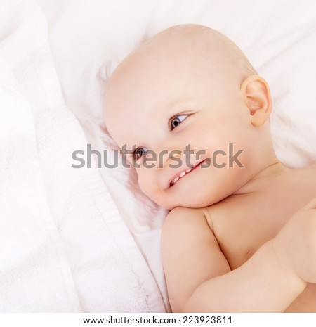 happy one year old baby in bed at home, top view - stock photo