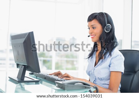 Happy operator typing on her computer in office - stock photo