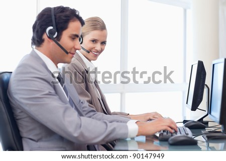 Happy operators using a computer in a call center