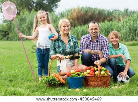 Happy ordinary family of four resting at countryside at summer day