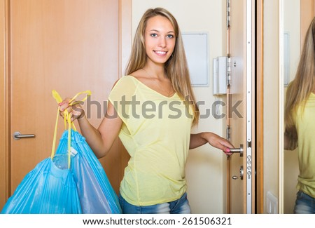 Happy ordinary woman staying at the door with trash bags - stock photo