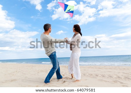 Happy outdoor autumn winter spring couple embracing and running on beach  a kite fly - stock photo