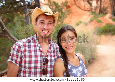 Happy outdoors couple portrait in american countryside. Smiling multiracial young couple in western USA nature. Man wearing cowboy hat and woman wearing USA flag shirt. - stock photo