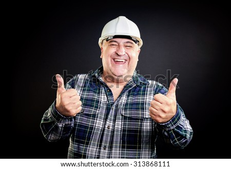 Happy overweight construction worker wearing safety equipment, thumbs up, white teeth. - stock photo