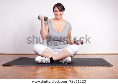 Happy overweight woman lifting weights - stock photo
