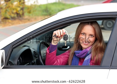 Happy owner of a new car showing a key. - stock photo