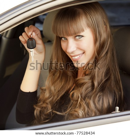Happy owner of a new  car showing the key - stock photo