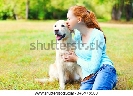 Happy owner woman kissing Golden Retriever dog on grass - stock photo