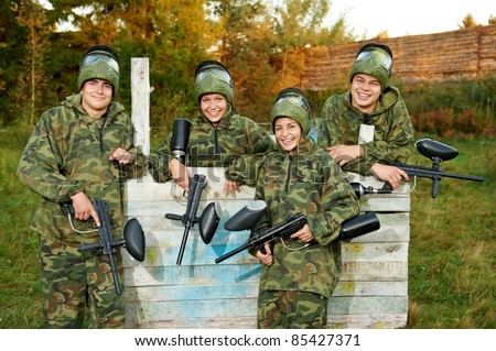 Happy paintball sport player girl in protective camouflage uniform and mask with marker gun outdoors