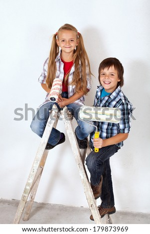 Happy painter kids on a old painting ladder - smiling and holding paint rollers - stock photo