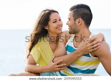 Happy pair having romantic date on sandy beach at sunny day