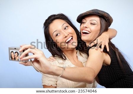 Happy pair of friends taking some pictures - stock photo