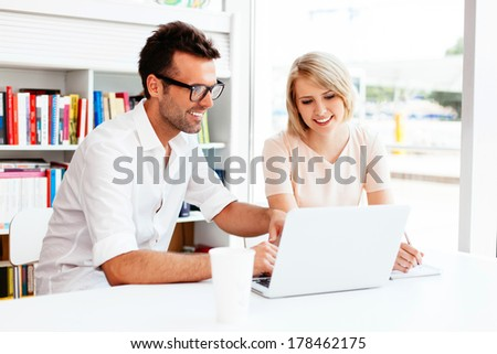 Happy pair of students discussing in front of a laptop - stock photo