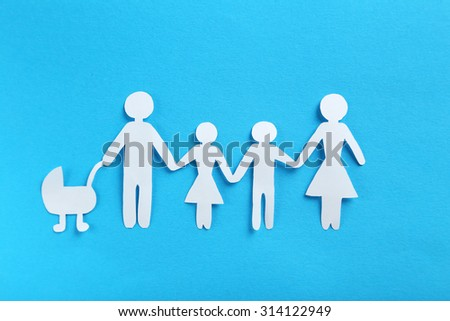 Happy paper family on blue background - stock photo