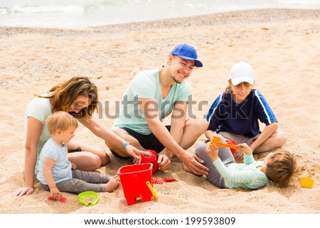 Happy parens with kids having a rest on sandy beach - stock photo