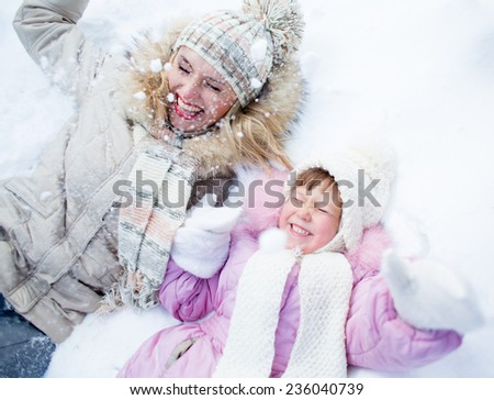Happy parent and kid lying on snow in winter outdoor - stock photo