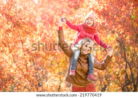 Happy parent and kid walking together outdoor in autumn park. Yellow and red tree leaves. Child sitting on her mother's neck. - stock photo