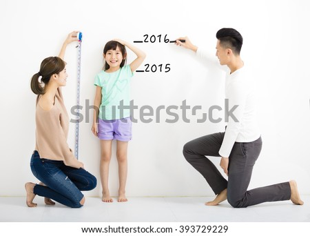 happy parent measures the growth of   daughter  - stock photo
