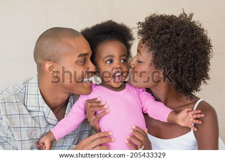 Happy parents and baby girl on bed together at home in the bedroom - stock photo