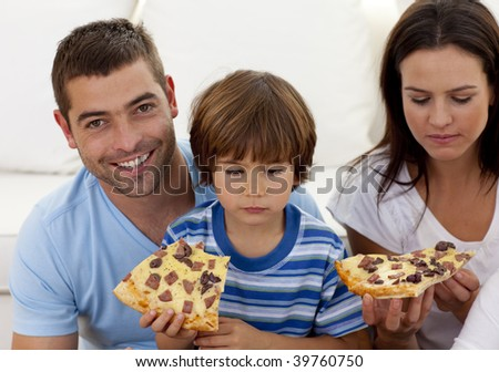 Happy parents and boy eating pizza in living-room all together