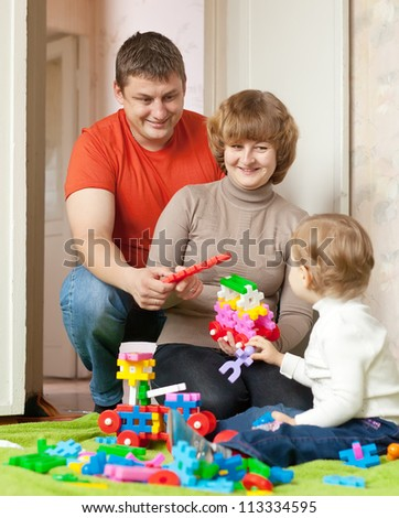 Happy parents and child plays with meccano set in home - stock photo
