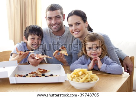 Happy parents and children eating pizza and fries at home - stock photo