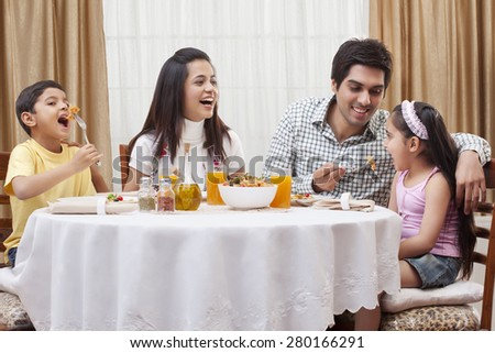 Happy parents and children eating pizza together at restaurant - stock photo