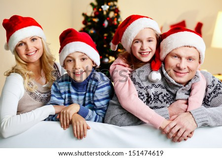 Happy parents and children sharing Christmas hugs - stock photo