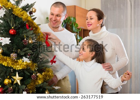 Happy parents and girl decorating Christmas tree in the living room at home - stock photo