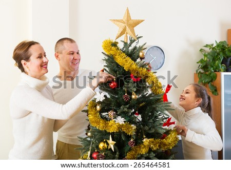 Happy parents and their child preparing for Christmas at living room  - stock photo