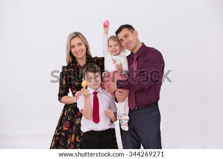 happy parents and their children are holding Easter eggs - stock photo