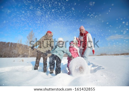 Happy parents and their kids in winterwear having fun outside - stock photo