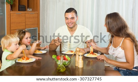 happy parents and two children  having lunch with pasta at home together