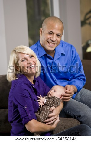 Happy parents cradling 3 month old baby on lap at home - stock photo